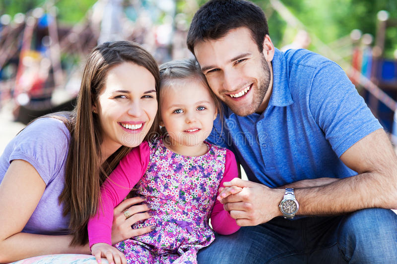 Family on playground. Happy family with little girl outdoors