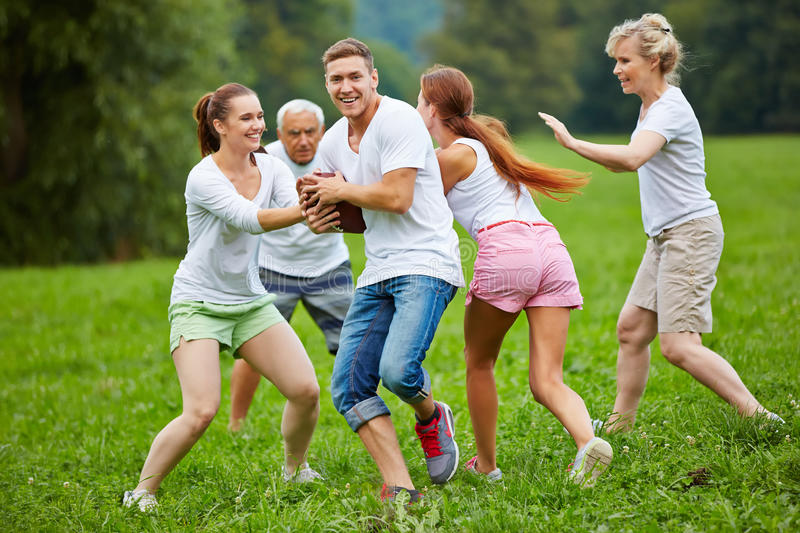 Family playing american football in garden. Smiling family playing american football on a meadow in their garden royalty free stock image
