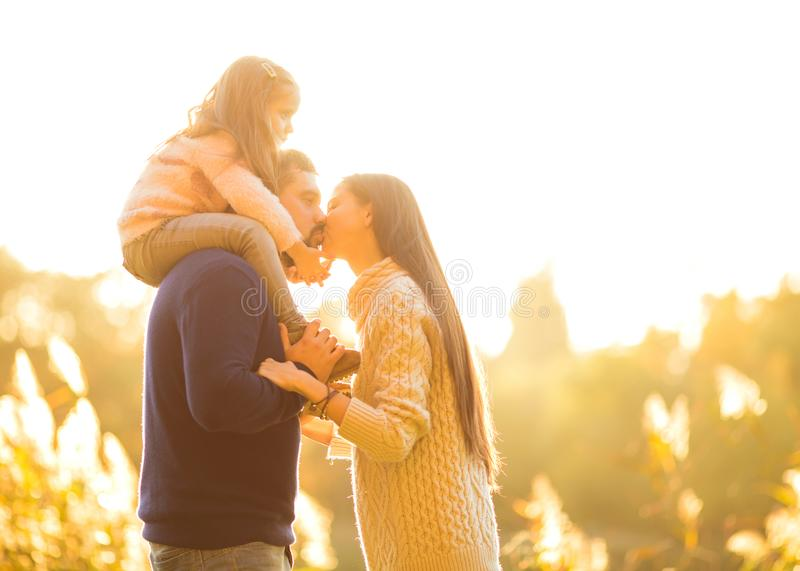 Family playing in autumn park having fun kisses royalty free stock image