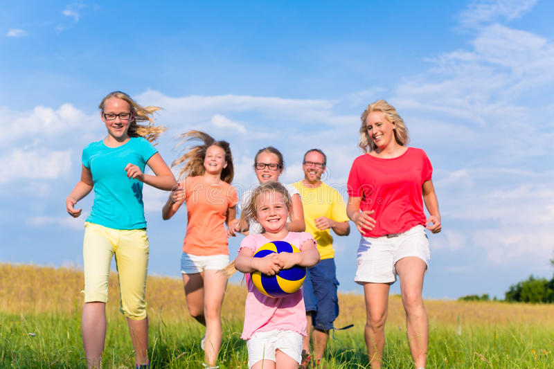 Family playing ball games on meadow. Running and having fun stock photo