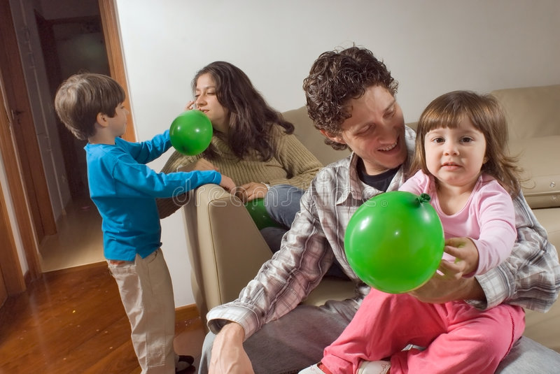 Family of Playing with Balloons. Horizontally framed indoor shot of a family of four playing with balloons on a sofa stock photos