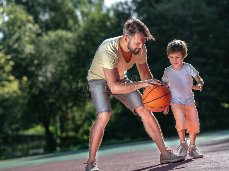 Family playing basketball outdoors. Father and son playing basketball outdoors royalty free stock image