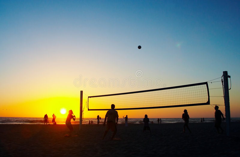 Family playing beach volleyball. In the evening royalty free stock photo