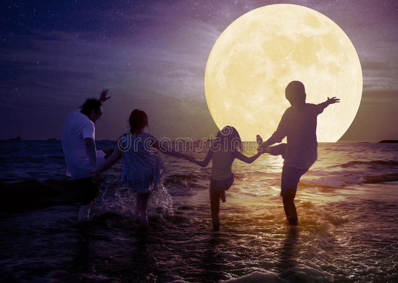 Family playing on beach and watching the moon.Celebrate Mid autumn festival concept royalty free stock photo