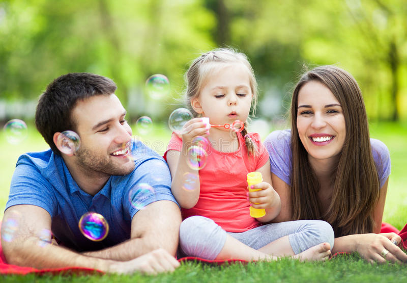 Family playing with bubbles outdoors. Happy family with little girl outdoors