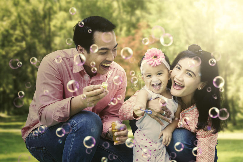 Family playing with bubbles in the park stock image
