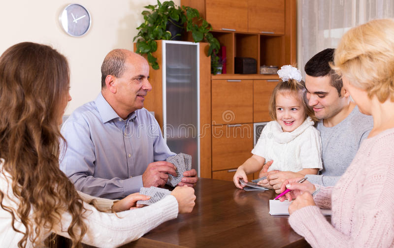 Family playing cards. Portrait of smiling multigenerational family playing cards stock photography