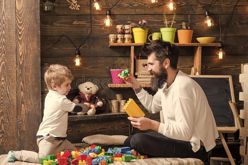Family playing with constructor at home. Dad and child play with toy cars, bricks. Nursery with toys and chalkboard on royalty free stock photography