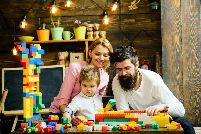 Family playing with constructor at home. Father helps to build wall out of toy bricks, plastic blocks. Mother watching royalty free stock photos