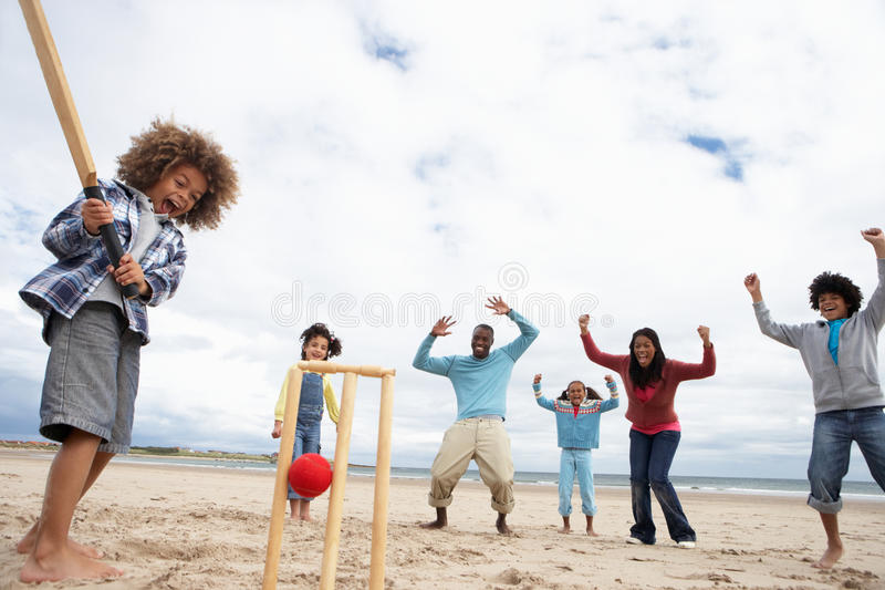 Family playing cricket on beach royalty free stock photography