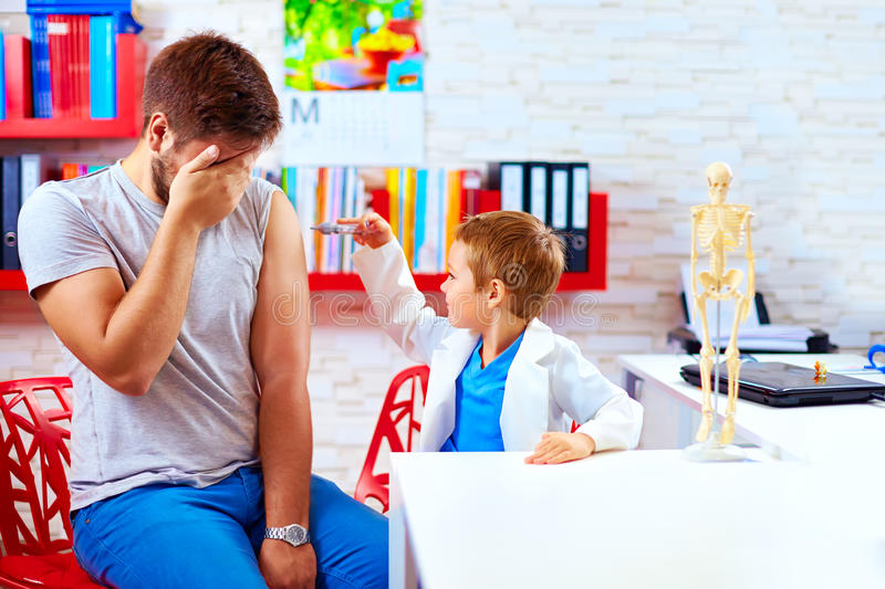 Family playing in doctor and patient, father scared of injection royalty free stock image