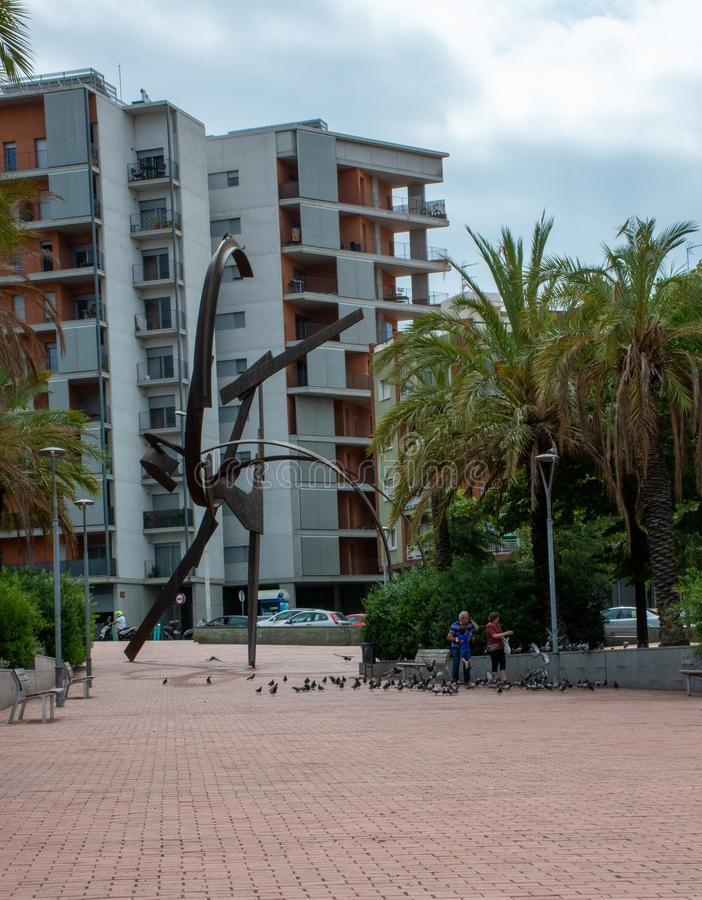 Family playing and feeding pidgeons next to sculpture in Barcelona. Barcelona, Spain - 26th July 2017 - Family playing and feeding pidgeons next to sculpture stock image