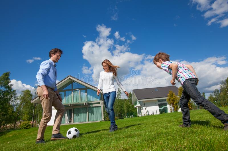 Family playing football. Family with of parents and son playing football on the backyard lawn near their house royalty free stock images
