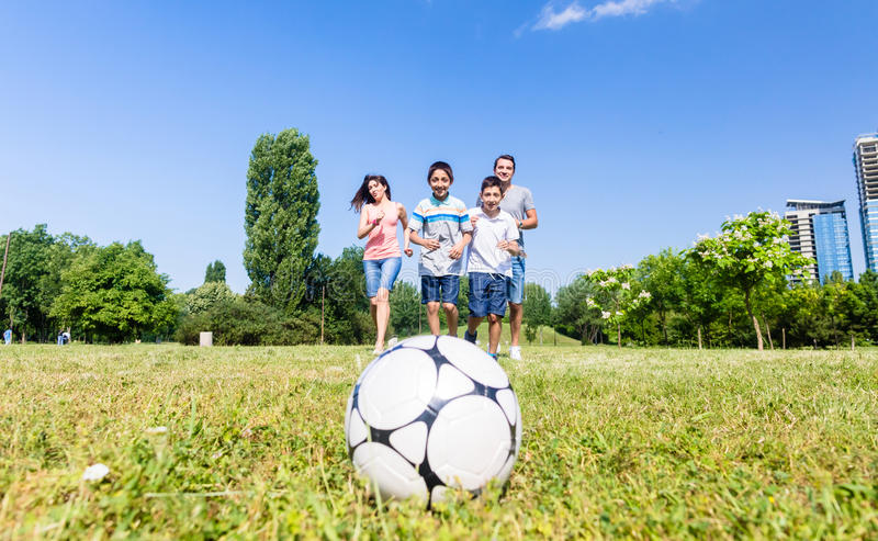 Family playing football or soccer in park in summer royalty free stock photography