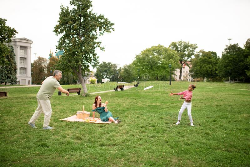 Family playing frisbee while having picnic in the park. Family playing frisbee. Happy good-looking family playing frisbee while having picnic in the park stock photography