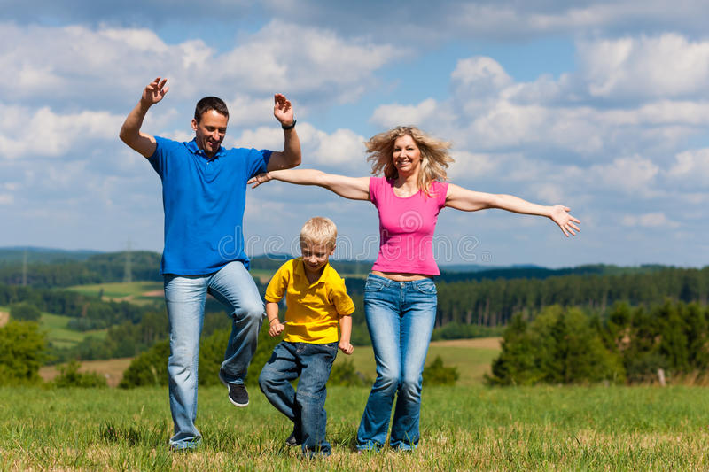 Family playing on meadow in summer stock photo