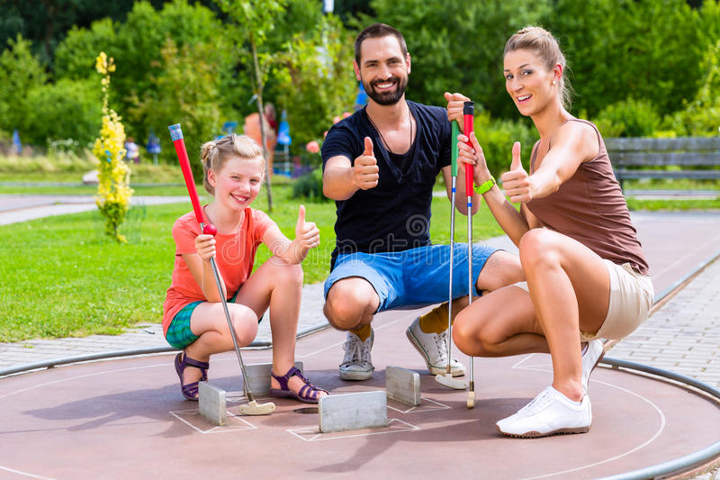 Family playing miniature golf on summer day royalty free stock photo