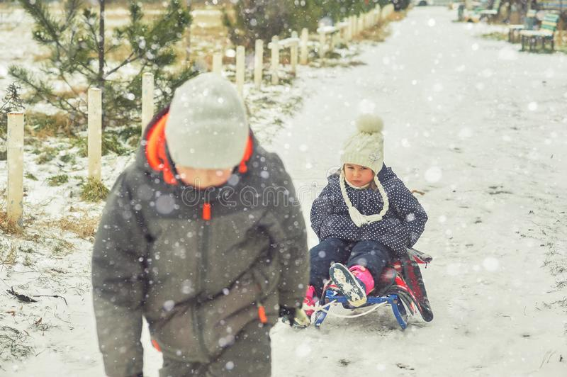 Family playing outdoors in the snow. Outdoor activities for family winter holidays. Winter fun in the fresh air . A little girl on a sled.Brother rubs sister stock images