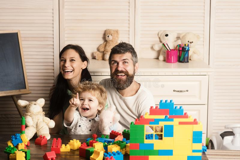 Family playing with plastic blocks and plush toys. Father, mother and son in playroom on light wooden background. Parents and kid with happy faces spend time royalty free stock photos