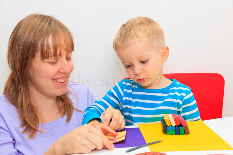 Family playing with play daugh. Mother and son playing with plasticine, early learning and daycare concept royalty free stock photography
