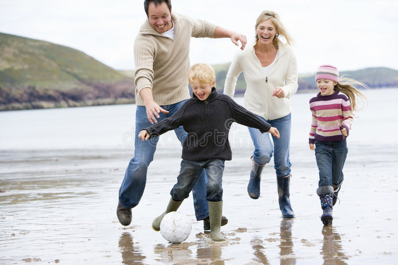 Family playing soccer at beach smiling.
