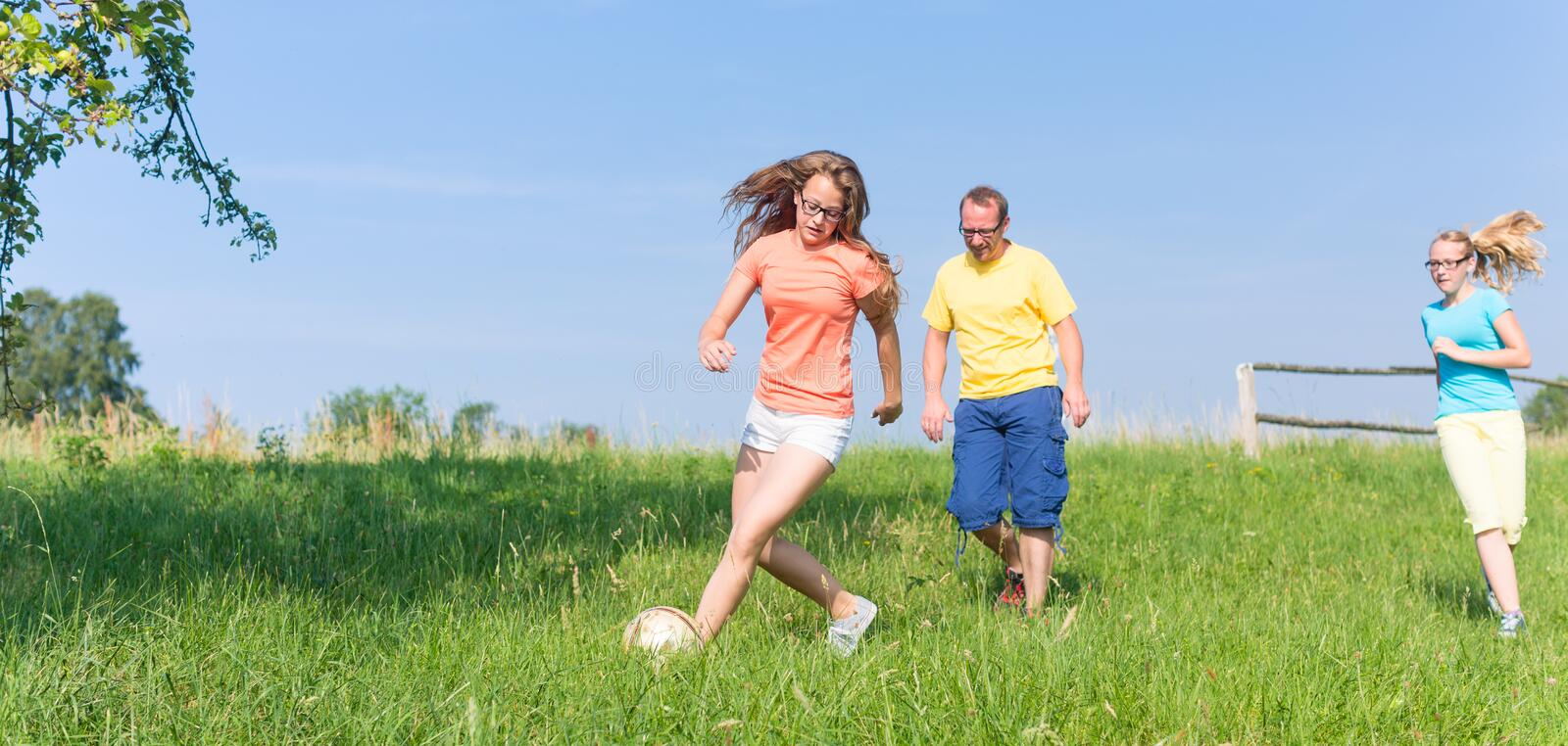 Family playing soccer on meadow in summer. Father and daughters playing soccer on meadow in summer stock photo