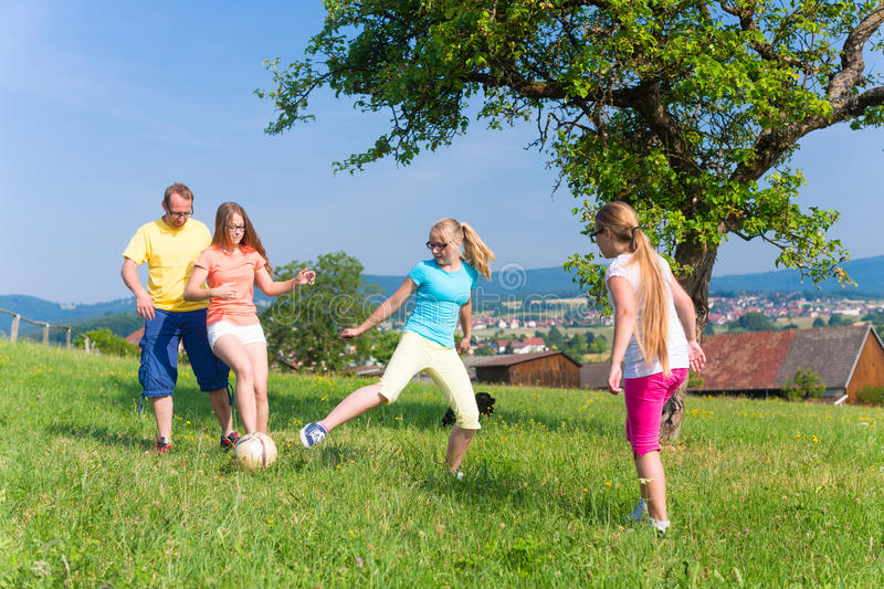 Family playing soccer on meadow in summer. Happy family playing soccer on meadow in summer stock photos