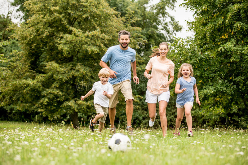 Family playing soccer in summer. With their children royalty free stock photo