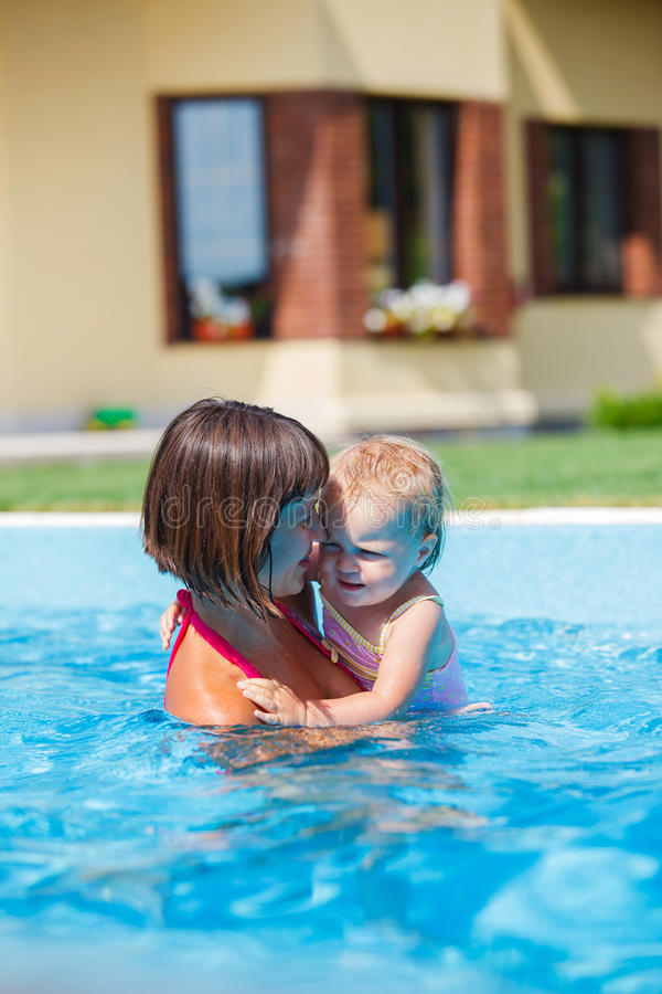 Family playing in swimming pool. Summer vacations concept. Happy mother and daughter playing in blue water of swimming pool stock photography