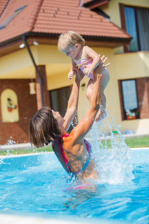 Family playing in swimming pool. Summer vacations concept. Happy mother and daughter playing in blue water of swimming pool royalty free stock photo