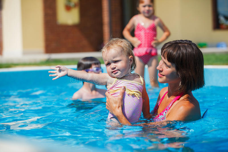 Family playing in swimming pool. Summer vacations concept. Happy mother and daughter playing in blue water of swimming pool royalty free stock images