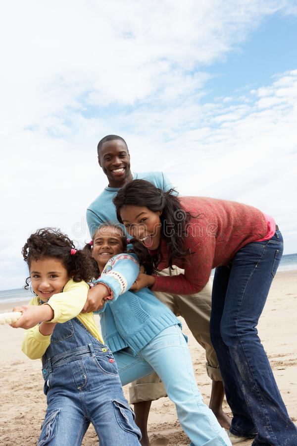 Family playing tug of war on beach royalty free stock photo