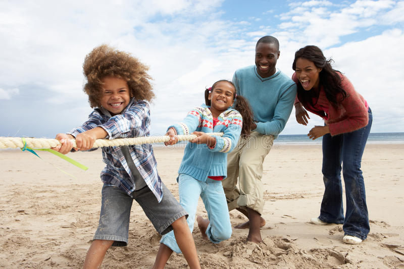 Family playing tug of war on beach stock photo