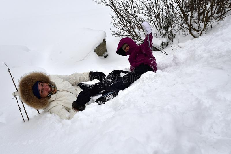 Family playing tumble on the snow in mountainsGirl with mother roll and trundle in high snow. Family to climb and tumble on the snow in mountains stock images