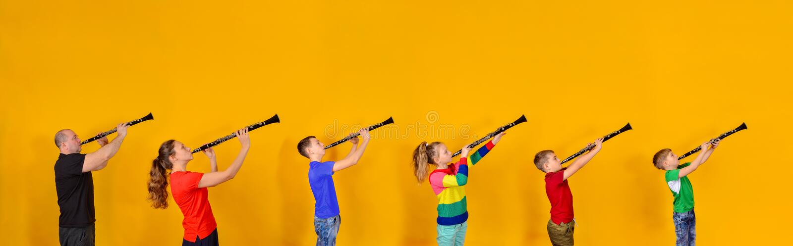 The family plays the clarinet. Father, mother and four children with clarinet on a yellow background. A wide-angle photo of six. People with musical themes royalty free stock images