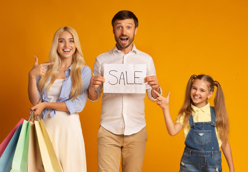 Family Pointing At Sale Sign Holding Shopping Bags, Studio Shot stock image