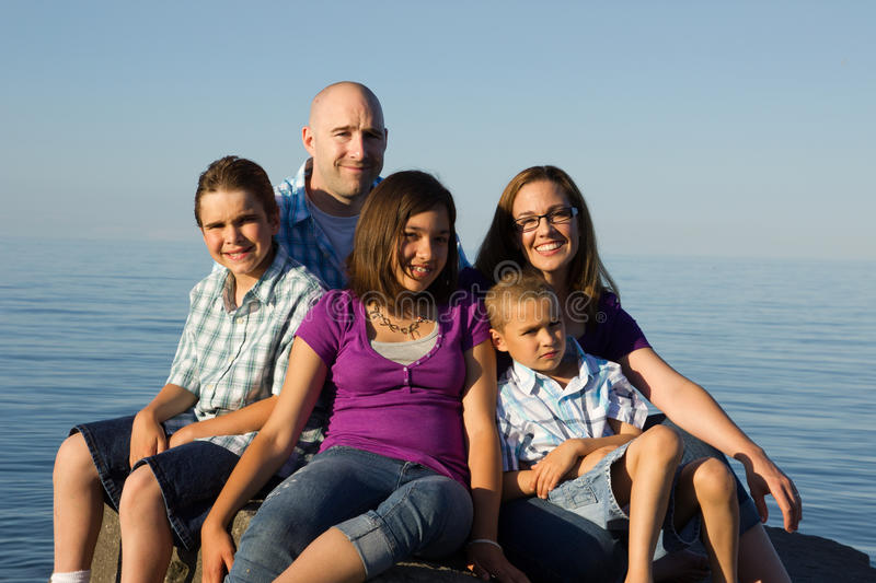Family Portrait. A family portrait on rock at the beach royalty free stock image