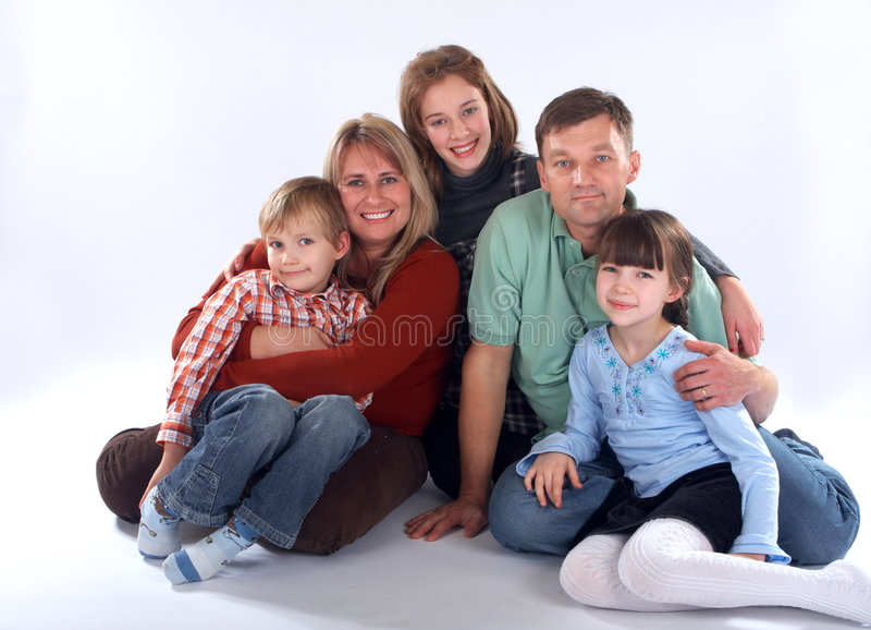 Family Portrait. Posed smiling portrait of a family of five, consisting of the parents and their three children, one boy and two girls. Isolated on a white royalty free stock photo