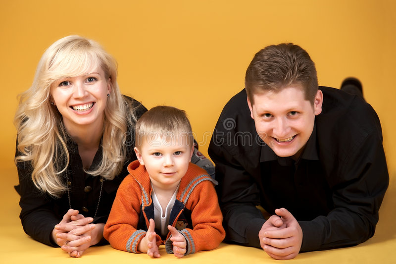 Family portrait. Happy family with baby on yellow background stock photography