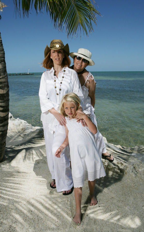 Family Portrait on the Beach. A family portrait on the beach in Florida. A mother, grandmother and daughter in white royalty free stock images