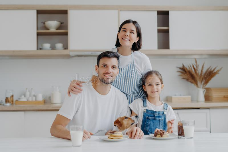 Family portrait of happy mother, daughter and father pose at kitchen during breakfast time, eat delicious homemade pancakes, their stock images