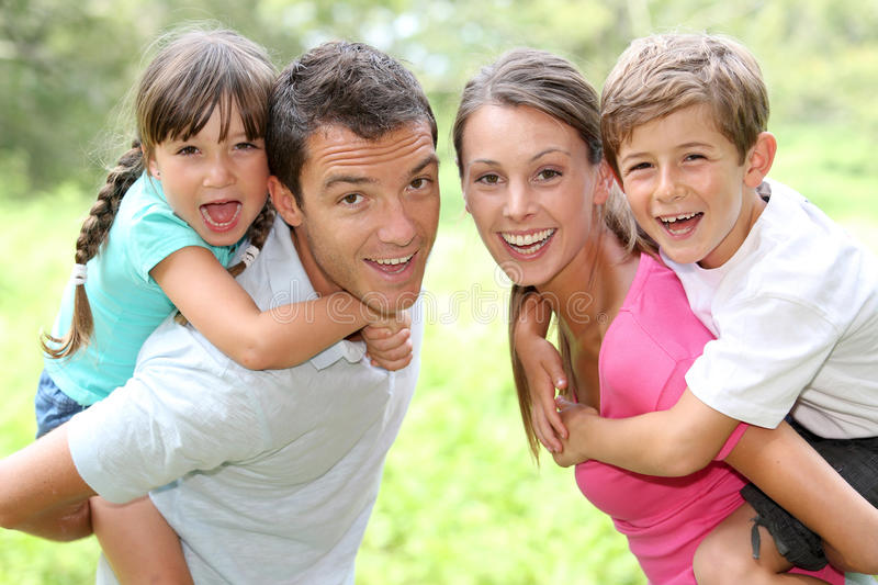 Family portrait. Portrait of happy parents holding kids on their back royalty free stock photo