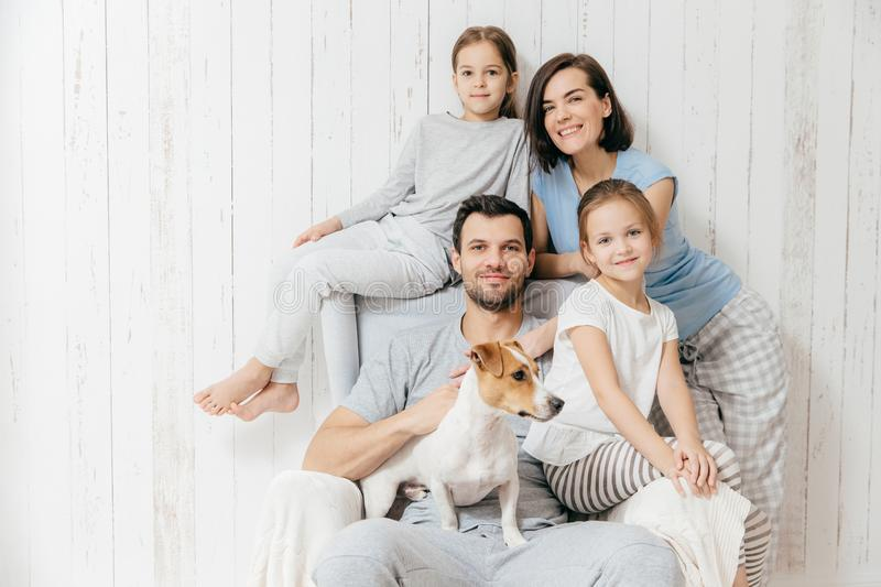 Family portrait. Happy parents with their two daughters and dog. Pose together against white background, spend free time at home, being in good mood. Mother stock photography