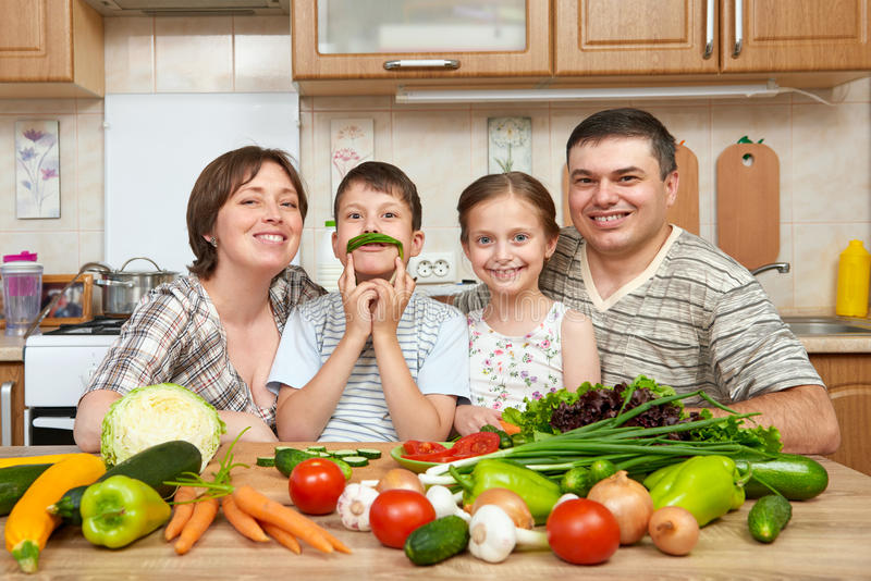 Family portrait in kitchen interior at home, fresh fruits and vegetables, healthy food concept, woman, man and children cooking an royalty free stock images