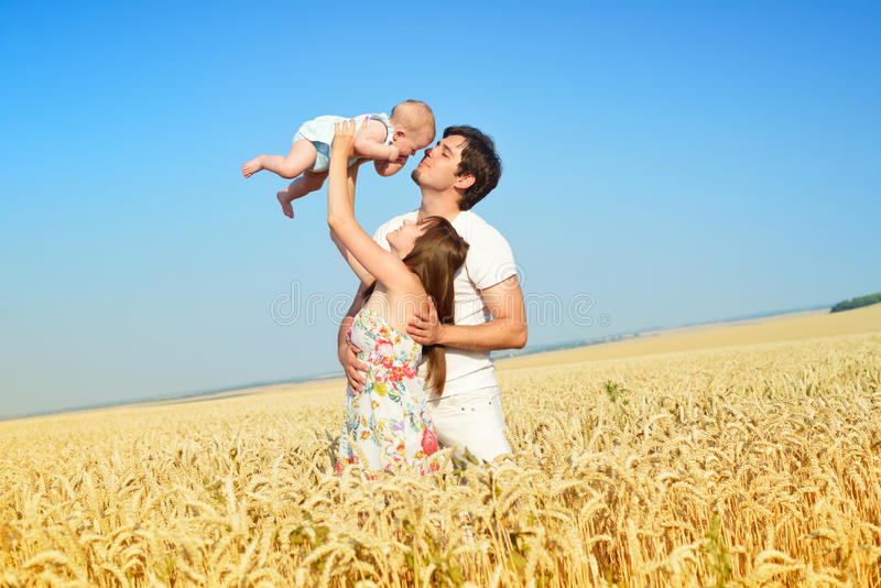 Family portrait. Picture of happy loving father, mother and their baby outdoors. Daddy, mom and child against summer blue sky. royalty free stock photos