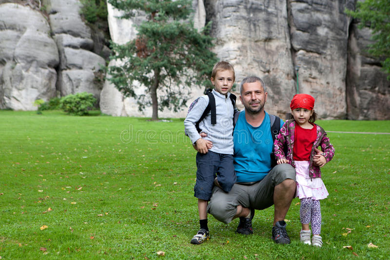 Family portrait beside rocks. Father and children pose for family photograph beside extensive rock face royalty free stock photography