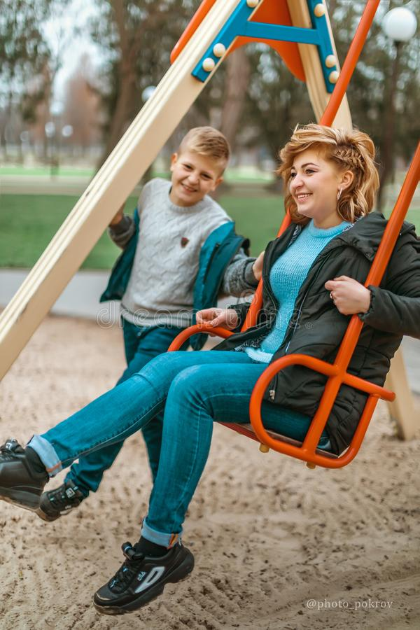 Family portrait young pretty happy mother and teenager son having fun on a swing in city park stock photography