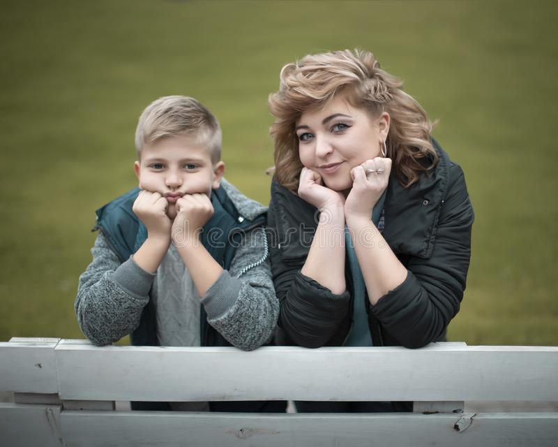 Family portrait young pretty mother and teenager son looking at camera in city park stock photography