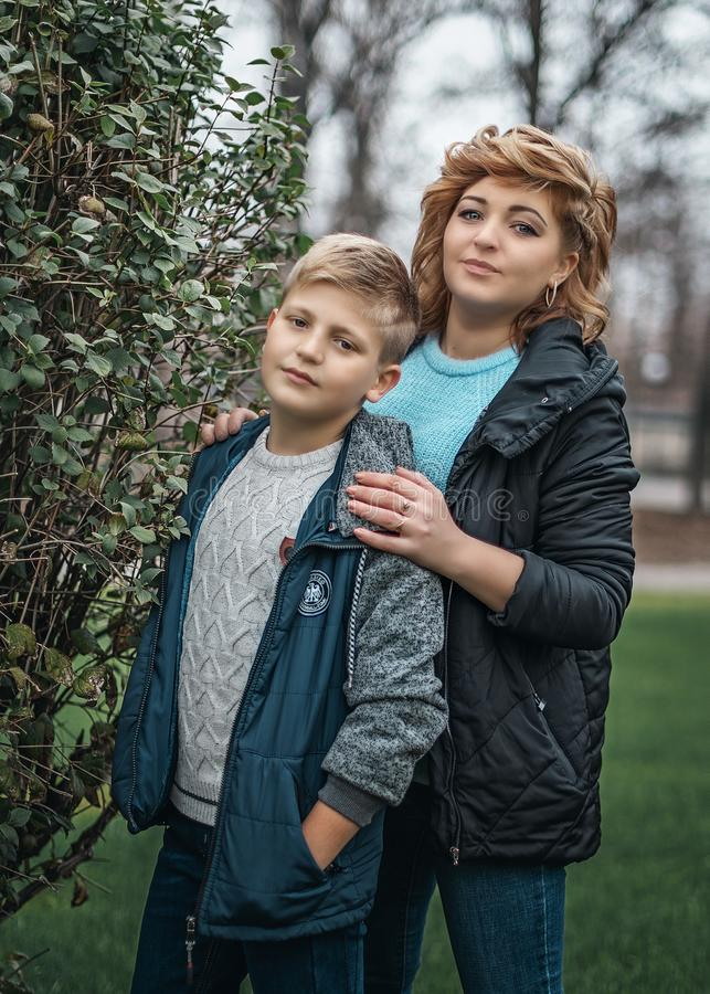 Family portrait young pretty mother and teenager son looking at camera in city park. Mother hugging her son`s shoulders royalty free stock photos