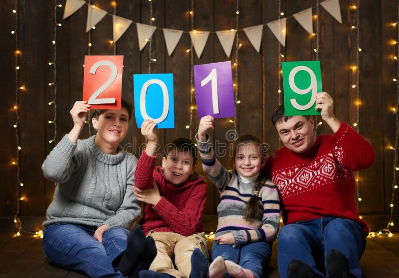 Family posing with 2019 new year text, sitting on dark wooden background with christmas lights and flags, and having fun. Winter h stock image